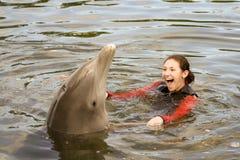Aantrekkelijke Vrouwelijke Tiener die met een Dolfijn zwemt Stock Afbeeldingen