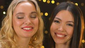 Aantrekkelijke vrouwen die glazen met champagne, Aziatische dame houden die aan camera knipogen stock footage