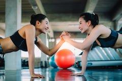 Aantrekkelijke vrouwen die in gymnastiek samen uitwerken Gezond, Sporten, Levensstijl, Fitness concept stock foto