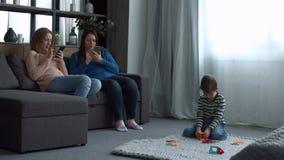 Aantrekkelijke vrouwen die op laag met smartphones ontspannen stock videobeelden