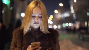 Aantrekkelijke vrouwen die slimme telefoon met behulp van terwijl het lopen in de stad bij nacht de stedelijke achtergrond van de stock footage