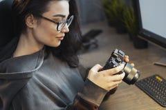 Aantrekkelijke vrouwen freelancer fotograaf het letten op foto's in camera thuis royalty-vrije stock foto's