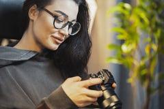 Aantrekkelijke vrouwen freelancer fotograaf het letten op foto's in camera thuis stock afbeeldingen