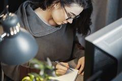 Aantrekkelijke vrouwen freelancer schrijver die over tekst denken en in notastootkussen schrijven royalty-vrije stock foto