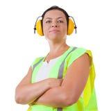 Aantrekkelijke Vrouwenarbeider in Veiligheidsjasje en Beschermend Oorhoofd Royalty-vrije Stock Afbeelding