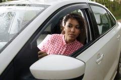 Aantrekkelijke vrouwenbestuurder terug en het parkeren auto die eruit zien royalty-vrije stock afbeelding