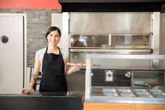 Aantrekkelijke vrouwenchef-kok die grote smakelijke pizza tonen terwijl status beh royalty-vrije stock afbeeldingen