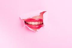 Aantrekkelijke vrouwenmond die een glimlach tonen door gescheurd karton Royalty-vrije Stock Foto's