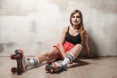 Aantrekkelijke vrouwenzitting op de vloer in rol het schaatsen het kijken royalty-vrije stock fotografie