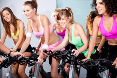 Aantrekkelijke wijfjes op fietsen in een geschiktheidsclub Royalty-vrije Stock Afbeeldingen