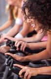 Aantrekkelijke wijfjes op fietsen in een gymnastiek Royalty-vrije Stock Foto