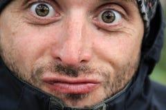 Aantrekkelijke witte Kaukasische mens met een varkenshaar crouches zijn gezicht: hij trekt grimassen, krult zijn lippen stock foto's