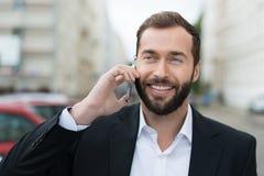 Aantrekkelijke zakenman die aangezien hij een vraag neemt glimlachen Royalty-vrije Stock Foto's