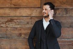 Aantrekkelijke zakenman die bij mobiele telefoon en het glimlachen spreken Stock Fotografie