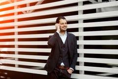 Aantrekkelijke zakenman die bij mobiele telefoon en het glimlachen spreken Royalty-vrije Stock Afbeelding