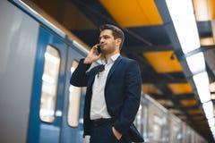 Aantrekkelijke zakenman die door mobiele telefoon spreken terwijl het wachten op trein in metro royalty-vrije stock afbeelding