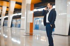 Aantrekkelijke zakenman die door mobiele telefoon spreken terwijl het wachten op trein in metro stock afbeeldingen