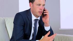 Aantrekkelijke zakenman die een telefoongesprek maakt stock video