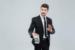 Aantrekkelijke zakenman in kostuum en band die u geldrug geven Stock Foto's