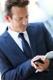 Aantrekkelijke zakenman in stad met telefoon en krant stock afbeeldingen