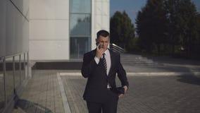 Aantrekkelijke zakenman in zwart kostuum die op smartphone tegen de achtergrond van commercieel centrum spreken openlucht stock videobeelden