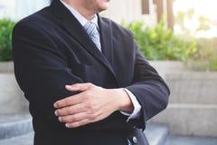 Aantrekkelijke Zekere zakenman die zich in een zwart kostuum bevinden keepin royalty-vrije stock afbeeldingen