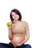Aantrekkelijke zwangere vrouw die een appel houdt Stock Foto's