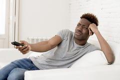 Aantrekkelijke zwarte Afrikaanse Amerikaanse de banklaag van de mensenzitting thuis het letten op televisie stock foto's