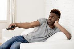 Aantrekkelijke zwarte Afrikaanse Amerikaanse de banklaag van de mensenzitting thuis het letten op televisie royalty-vrije stock afbeelding