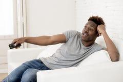 Aantrekkelijke zwarte Afrikaanse Amerikaanse de banklaag van de mensenzitting thuis het letten op televisie stock foto