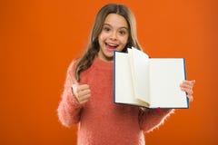 Aanvang om meer te leren Het boek oranje achtergrond van de meisjesgreep Het kind toont open pagina's van boek of blocnote Boekha royalty-vrije stock afbeeldingen