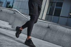 Aanvang te lopen Besnoeiingsmening van mannelijke spiervoeten in zwarte sportkleding en tennisschoenen die tegen moderne stad lop royalty-vrije stock foto's