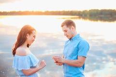 Aanzoek op zonsondergang de jonge mens doet een voorstel van betrothal aan zijn meisje op het strand stock fotografie