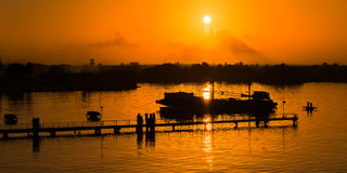 Aard van de het silhouet de oranje hemel van de zonsondergangpier door het overzees Stock Afbeeldingen