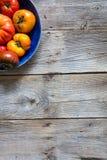 Aardachtige gehalveerde plaat van gekleurde gebarsten erfgoedtomaten over hout Stock Afbeeldingen