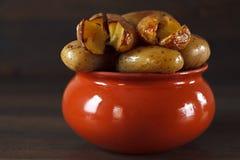 Aardappel in de schil in een kleipot op een achtergrond van houten su Stock Afbeeldingen