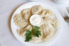 Aardappel-gevulde varenyky op een witte plaat op witte lijstvareniki met zure room stock foto's