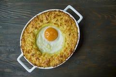 Aardappelbraadpan met bolognese Aardappel in de schilbraadpan met ei en geraspte kaas in een ceramisch ovaal bakselblad Houten da royalty-vrije stock foto