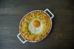 Aardappelbraadpan met bolognese Aardappel in de schilbraadpan met ei en geraspte kaas in een ceramisch ovaal bakselblad Houten da stock afbeelding