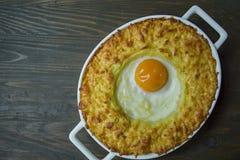 Aardappelbraadpan met bolognese Aardappel in de schilbraadpan met ei en geraspte kaas in een ceramisch ovaal bakselblad Houten da royalty-vrije stock foto's