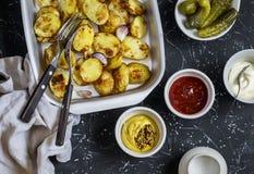 Aardappelen in de schil en saus hem - eigengemaakte mayonaise, ketchup en mosterd Heerlijke lunch of snack royalty-vrije stock fotografie