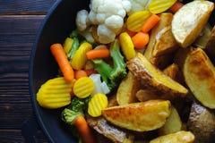 Aardappelen in de schil met groenten in een pan op een houten achtergrond stock afbeelding