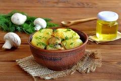 Aardappelen in de schil met paddestoelen en dille in een kleikom Royalty-vrije Stock Foto