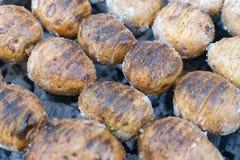 Aardappelen in de schil op de steenkolen op de grill met een Gouden voorbereiding van het korstvoedsel stock foto