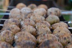 Aardappelen in de schil op de steenkolen op de grill met een Gouden voorbereiding van het korstvoedsel royalty-vrije stock afbeeldingen