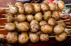 Aardappelen in de schil op vleespennen worden geroosterd die Stock Foto's