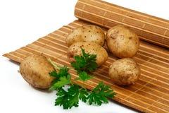 Aardappelknollen met een twijg van peterselie op de mat Stock Fotografie