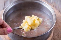 Aardappels in een lepel in soep Stock Afbeeldingen