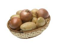 Aardappels en uien op de rieten mand Stock Foto's