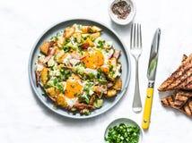 Aardappels, ham, de knoeiboel van het eierenontbijt op een lichte achtergrond, hoogste mening Heerlijk, voedzaam ontbijt, snack stock afbeeldingen
